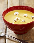 Bowl of Cheddar Cheese Beer Soup with Popcorn Garnish