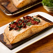 Cooked Cedar Planked Salmon Fillet with Sun Dried Tomato and Parsley