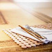 Besteck, Essstäbchen und Serviette auf Tischset