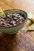 Bowl of Black Bean Dip with Chips on Wood Table