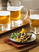 Plate of Nachos with Mugs of Beer