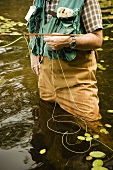 Man Standing in Water Fishing with Fly Fishing Pole