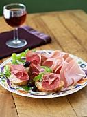 Vorspeise mit Mortadella, Schinkenbrötchen und Oliven