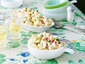 Bowl of Pasta Salad on Tabled with Serving Bowl and Drinks