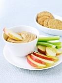 Kleiner Snack mit Erdnussbutter-Dip, Apfelspalten und Stangensellerie