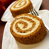 Two Slices of Pumpkin Spice Roll on White Plates; Fork