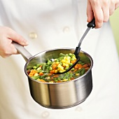 Hand Holding Spoon and Pot of Mixed Vegetables
