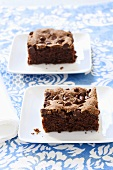 Two Pieces of Chocolate Zucchini Cake on White Plates