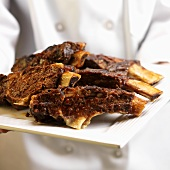 Person Holding Plate of Beef Ribs