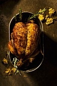 Roasted Game Hen with Wild Flowers and Rosemary in Pan