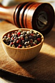 Red, Green, White and Black Peppercorns in Wooden Bowl with Pepper Grinder