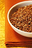 Bowl Of Flax Seeds On Orange Napkin