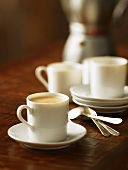 Cup of Cuban Coffee in White Mug on Sauce; Spoons and Mugs