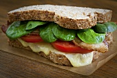 Bacon, Tomato and Spinach Sandwich with Melted Cheese on Whole Wheat Bread