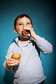 Little Boy Eating a Blueberry Muffin and Holding a Second