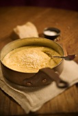 Creamy Polenta with Cheese in a Pot with Spoon