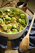 Bowl of Brussels Sprouts with Bacon and Walnuts; Wooden Spoon