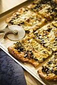 Rectangular Pizza Topped with Greens and Havarti Cheese; Sliced