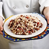 Hands Holding a Plate of Red Beans and Rice