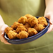 Hands Holding a Plate of Hush Puppies