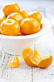 Unpeeled clementines in bowl, peeled clementine in front