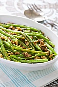 Green beans with spicy nuts in serving dish