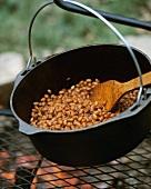 Baked Beans im Kessel über Feuer