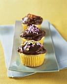 Yellow Cupcakes with Chocolate Frosting and Colored Sprinkles