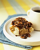 Sticky bun with caramel sauce and pecans, served with coffee (USA)