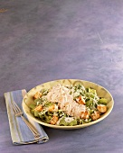 Chicken Caesar Salad in a Bowl; Cloth Napkin and Fork