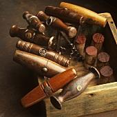 Verschiedene antike Korkenzieher und Weinkorken in Holzkiste