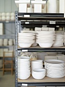 Stacked White Ceramic Dishware on Shelves