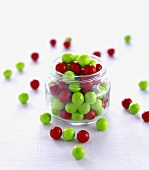 Red and Green Chocolate Balls in and Around a Glass Jar