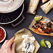 Tamales with tomato salsa and black beans being prepared
