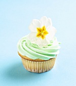 Cupcake with Green Butter Cream Frosting and Primrose Garnish
