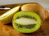 Halved and Whole Kiwi on Cutting Board; Knife