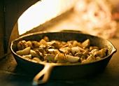 Kartoffeln in Gusseisenpfanne im Holzofen