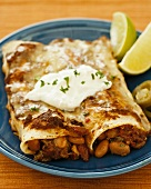 Two Beef and Bean Enchiladas on a Plate with Sour Cream