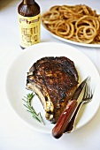Rib Eye Steak on a White Plate; Rosemary Sprig; Knife and Fork; Onion Rings