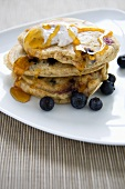Wholemeal Blueberry Pancakes with Butter and Maple Syrup; On White Plate