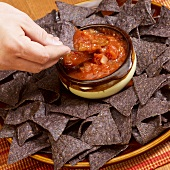 Hand Dipping Blue Corn Chip into Salsa