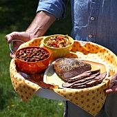 Man Holding Platter with Grilled Tri Tip Roast, Baked Beans and Salsa