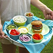 Person Carrying a Tray with a Hamburger and Toppings
