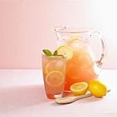 Pitcher und Glas mit pinker Limonade, Holzlöffel und Zitronen