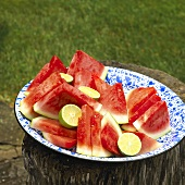 Dish of Watermelon Wedges with Limes on a Stump Outdoors