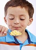 Kleiner Junge hält Löffel mit Macaroni and Cheese