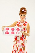 Frau im 50er-Jahre-Stil serviert Snowball Cupcakes (USA)