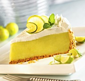 Slice of Key Lime Pie on a White Plate; Lime Wedges