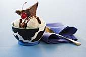 Ice Cream Sundae in a White and Black Bowl; Blue Napkin and Spoon