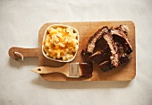 Sliced Barbecue Pork Ribs and Mac and Cheese on Cutting Board